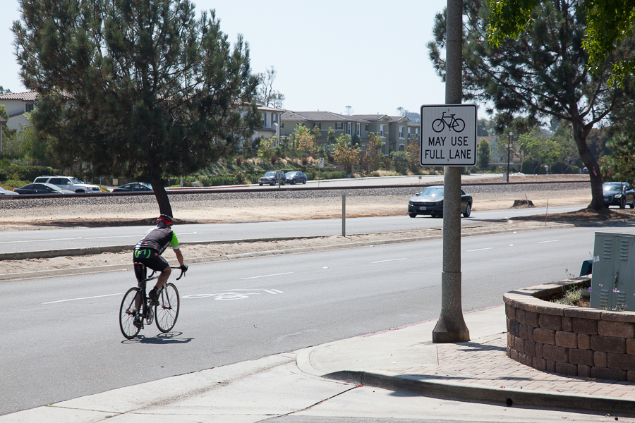 "Cyclist riding on highway 101 near ""Bikes May Use Full Lane"" sign in Leucadia, California"